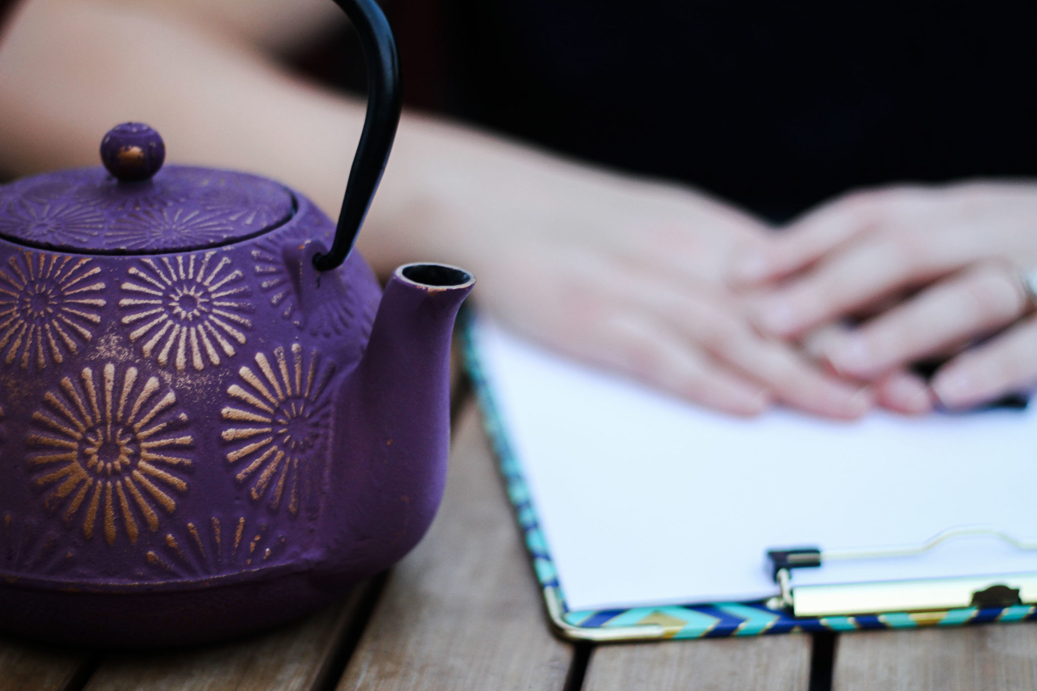 a pot of tea and clipboard in front of a woman ready for a consultation with a client